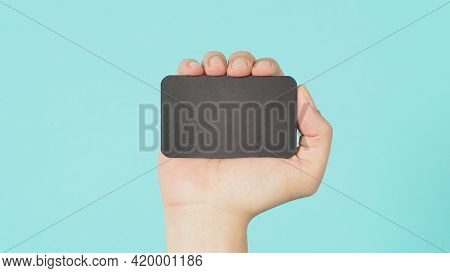 Empty Space For Text.male Hand Holding Black Blank Card Isolated On Mint Green Or Tiffany Blue Backg