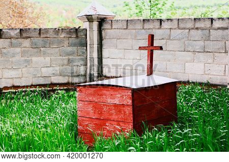 Wooden Box On The Graveyard . Religious Cross Painted In Red