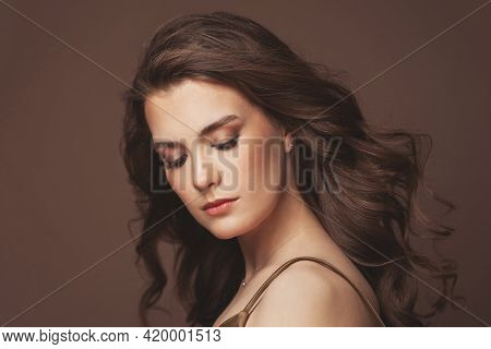 Portrait Of Young Woman Brunette With Clear Skin And Healthy Wavy Hair On Brown Background. Beautifu