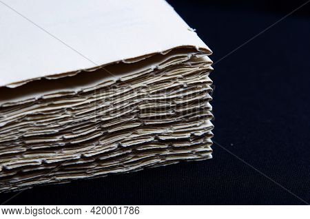 The Process Of Book Binding; Close Up Of Stacked Paper Folders. Black Background