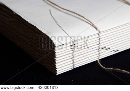 The Process Of Book Binding; Close Up Of A Raw Book After Sewing On Cords. Black Background