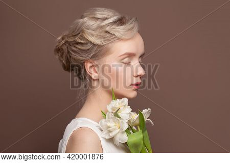 Magnificent Young Woman With Bridal Hairstyle And White Tulip Flowers On Brown Background