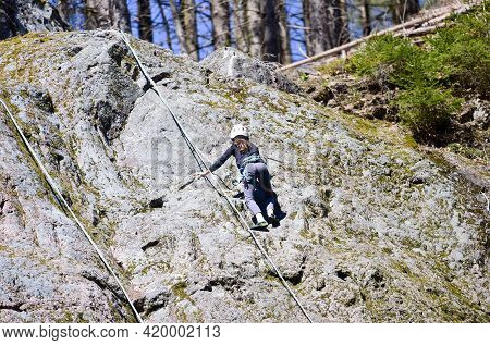 A Young Girl Is Climbing A Rock. A Girl With A Rope Engaged In The Sports Of Rock Climbing On The Ro