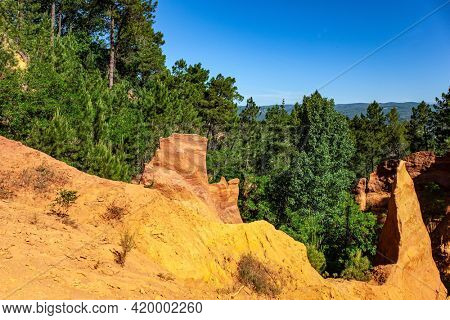 Now the rocks have grown into dense forests. The village of Roussillon. Bizarre ocher rocks. France, Provence. Walk along the most beautiful red-yellow-orange route.