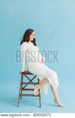 Cute Smiling Pregnant Woman In White Dress Resting On Wooden Chair On Blue Background