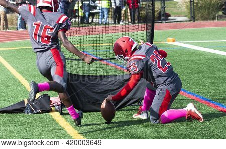 Rear View Of A High School Football Field Goal Kicker On The Sidelines During A Game Warming Up Kick