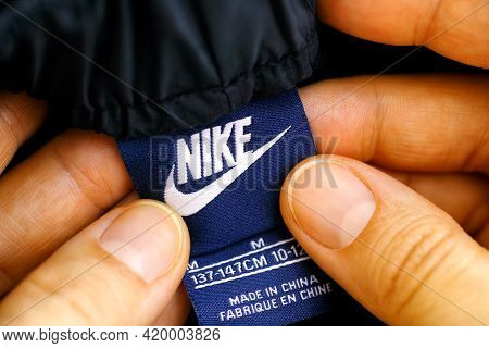 Tambov, Russian Federation - April 03, 2021 Woman Hands With Nike Kids Sweatpants Clothes Label.
