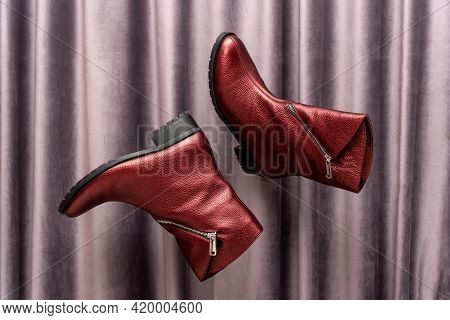 Levitating Shoes. Red Leather Womens Boots Flying In Air Against Grey Draped Textile Fabric Or Curta
