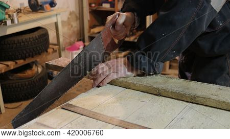 A Hacksaw In The Process Of A Carpenter's Work In A Workshop Atmosphere, A Carpenter Manually Saws A