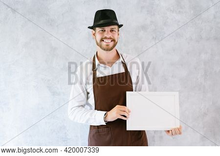 Small Business Owner Smiling In Barista Apron Holding Empty Sign - Ready To Insert Text Against Back