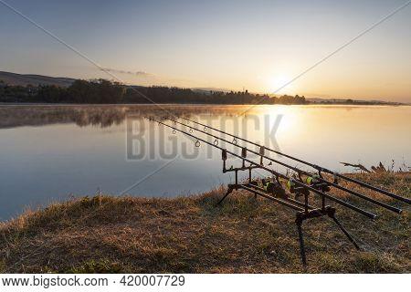 Carp Fishing Rods With Carp Bite Indicators And Reels Set Up On Rod Pod Near Lake River. Fishing Dur