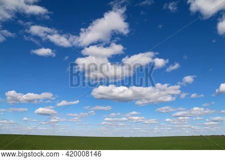 Bright Country Farm Green Grass Field With Fluffy White Clouds Cloudscape As A Landscape Nature Scen