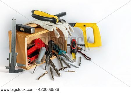 Construction Tools Lie In A Wooden Box And Next To It On A White Background.