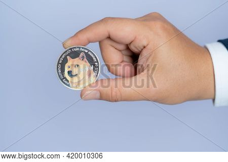 Dogecoin Doge Included With Cryptocurrency On Hand Business Man Wearing A Blue Suit. Filed And Put A