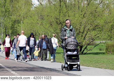 Moscow, Russia - May 2021: Crowd Of People Walking In Park. Lonely Young Woman With Pram In The Fore