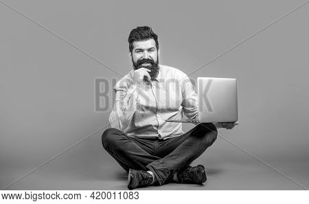 Young Businessman Using His Laptop, Pc. Happy Young Man Sitting On The Floor With And Using Laptop C
