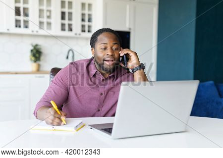 Multitasking And Busy African-american Male Entrepreneur Using Laptop Computer, Talking On The Smart