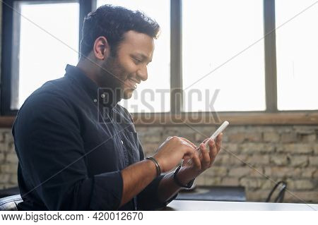 Serene Indian Guy Using Smartphone For Websurfing, Smiling Mixed-race Guy Browsing, Scrolling News F