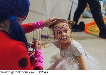 Little Girl Getting Her Face Painted In Butterfly Shape By Face Painting Artist. Make Up. Real Peopl