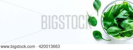 Fresh Green Spinach Leaves In Glass Bowl On White Table.