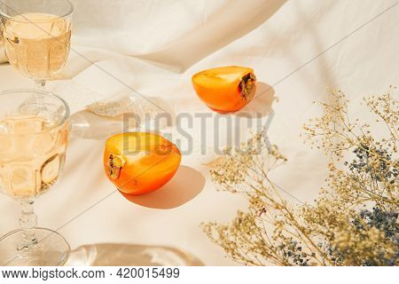 Halfs Of Persimmon Fruits And Two Glasses With Lemonade On Pastel Background With White Cloth And Su