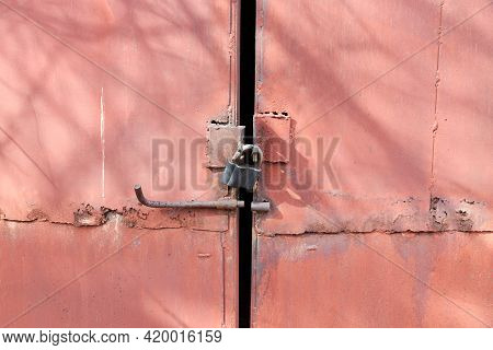 Old Rusty Metal Gate With A Bolt Latch And Padlock