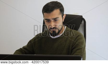 Man Is Working Intently At Laptop In Office. Hdr. Handsome Man Is Working At Laptop In Sweater. Free