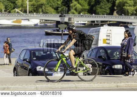 Stockholm, Sweden - July 06, 2017. Woman In Helmet And Tracksuit Rides Bicycle Along The Sea Embankm