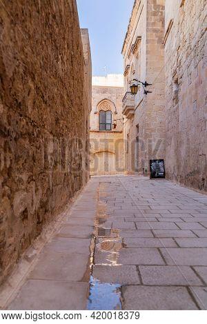 Mdina, Malta - February 18, 2010. Narrow Street Of Mdina, Ancient Capital Of Malta. Beige Stone Wall
