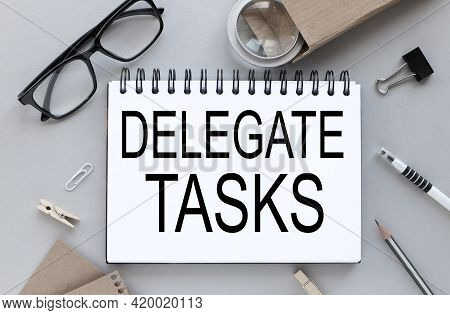 Delegate Tasks. Gray Background. Text On Notepad Near Glasses With Pen And Pencil. Business Layout.