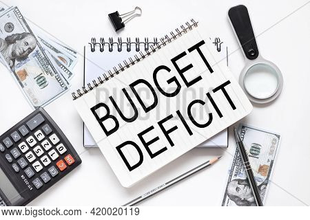 Budget Deficit. Notebook On White Workspace. Near The Notepad Dollar Bills And A Calculator