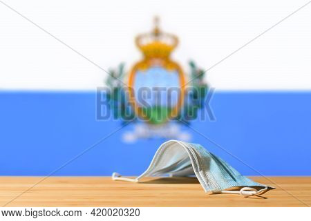 A Medical Mask Lies On The Table Against The Background Of The Flag Of San Marino. The Concept Of A