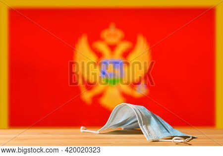 A Medical Mask Lies On The Table Against The Background Of The Flag Of Montenegro. The Concept Of A