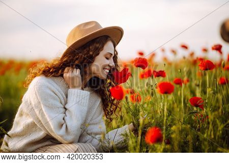 Beautiful Girl Posing In A Poppy Field. Young Woman In A Hat With Long Curly Hair In A Poppy Garden.