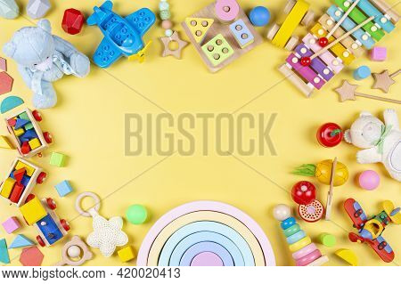 Baby Kids Toys Frame. Colorful Educational Wooden Plastic And Fluffy Toys For Children On Pastel Yel