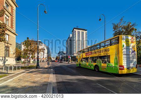 VIENNA, AUSTRIA - SEPTEMBER 28, 2018: Yellow sightseeing tour bus under blue sky on the street of Vienna - austrian capital, famous and popular tourist destination.