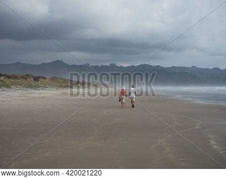 Elderly Couple Walking Along Pacific Ocean Waiau Sand Beach In Bay Of Plenty Coromandel Peninsula No