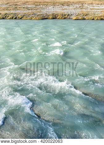 Turquoise Waters With White Foam And Bank With Grass Of Sochi River.. Mountain River With Clear Wate