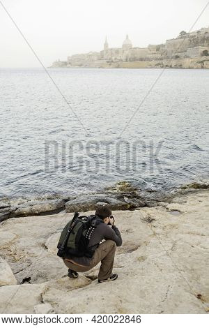 Photographer Takes Picture Of Something While Kneeling On Rock By Sea. Man Travels Around Island Of