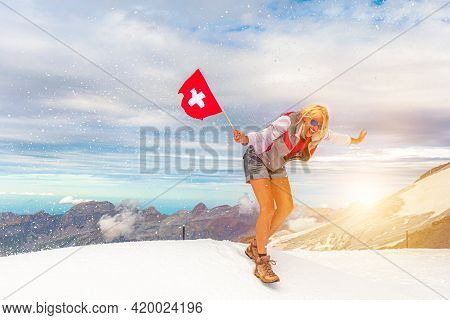 Woman With A Swiss Flag On Titlis Cliff In A Snow Storm. Top Of Titlis Mountain In The Uri Alps At 3