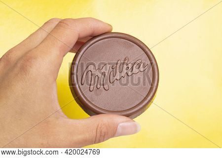 Belarus, Novopolotsk - 09 May, 2021: Round Waffle Milka In Hand On Yellow Background