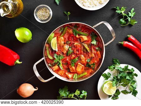 Thai Style Red Chicken Curry With Vegetables In Pan Over Black Stone Background. Top View, Flat Lay