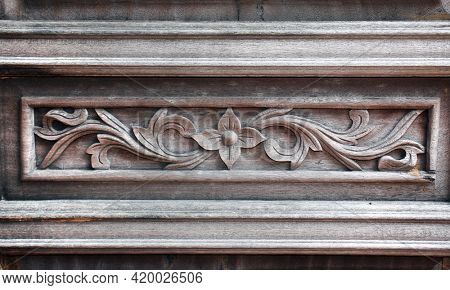 Horizontal background with wood carving floral ornament. Ancient decorative carved border on wooden surface