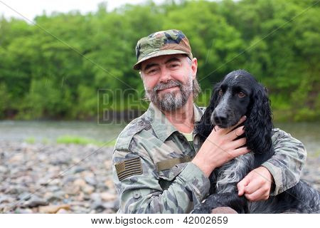Middle aged man with a dog (Russian Hunting Spaniel). At river in the rain.