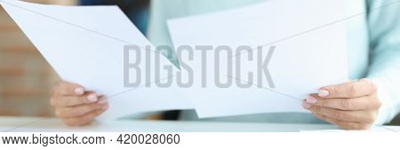Female Hands Hold Documents Over Work Table