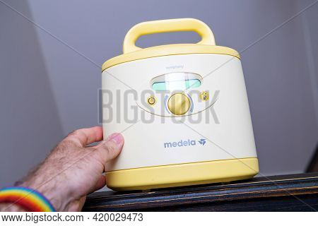 Paris, France - May 7 2021: Pov Male Hand Holding Hero Object Of New Medela Simphony Made In Switzer