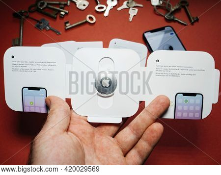 Paris, France - May 2, 2021: Man Holding Unboxed Pack With New Airtag - Small Device Helps People Ke