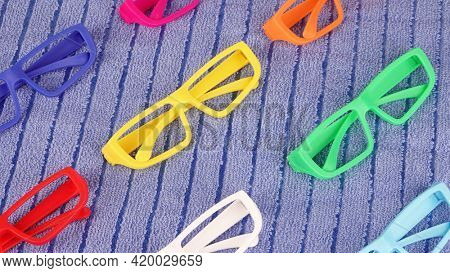 Colorful glasses sunglasses frames on blue summer towel pastel colors abstract beach concept photo
