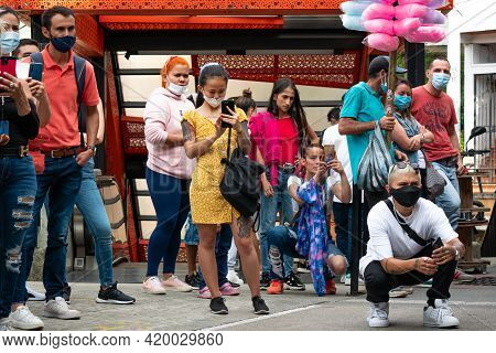 Medellin, Antioquia, Colombia - March 27 2021: Young Asian Woman Is Taking Pictures In The Middle Of