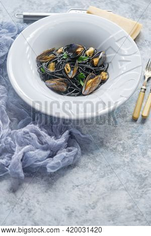 Black seafood spaghetti pasta with mussels over stone background. Mediterranean delicious food